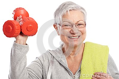 Energetic elderly woman with dumbbells smiling