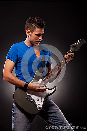 A young man playing guitar with great emotions