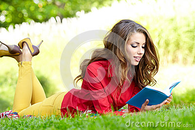 Woman lays on green field and reads book.