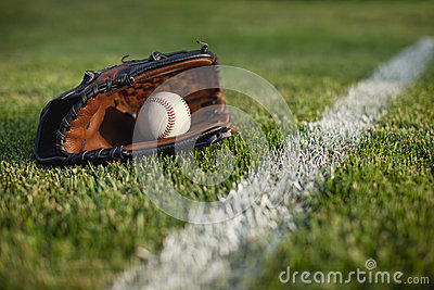 Baseball mitt and ball on field with white line