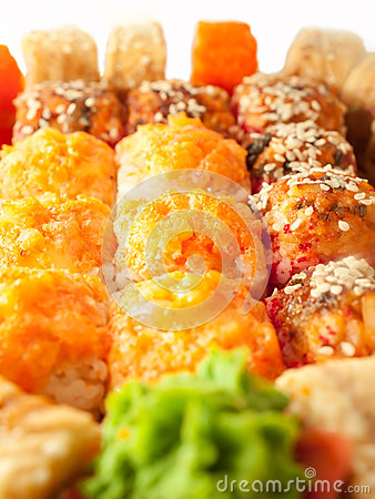 Baked sushi rolls with orange and red roe closeup