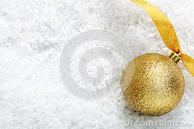 Gold glitter bauble on snow