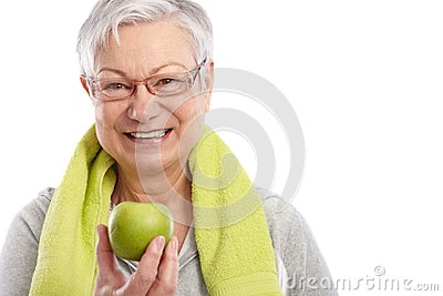Healthy old woman with green apple smiling