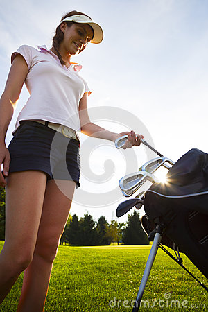 Golfer taking out iron from golf bag.