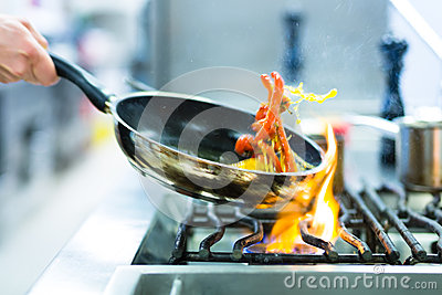 Chef in restaurant kitchen at stove with pan