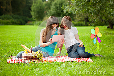 Two women in the park on a picnic with a Tablet PC