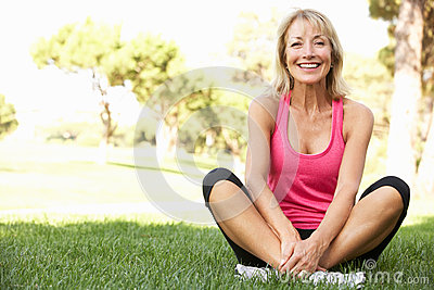 Senior Woman Resting After Exercising In Park