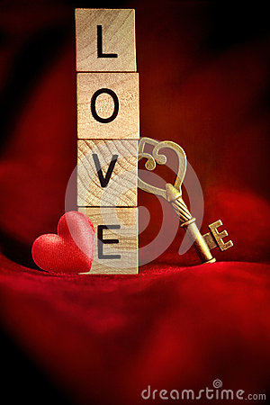 Gold key with wooden letters that spell the word love