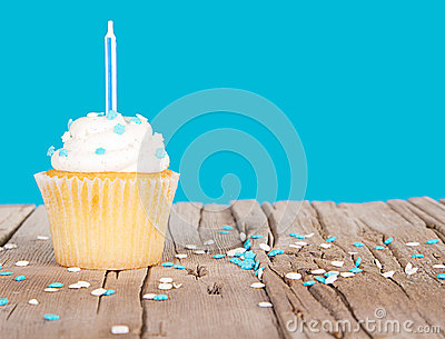 Single cupcake with blue candle and sprinkles