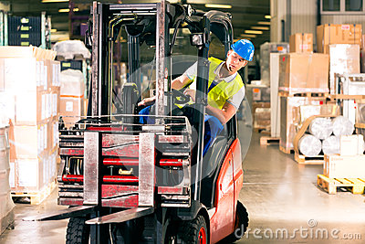 Forklift driver at warehouse of forwarding
