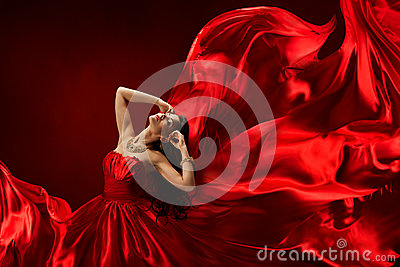 Woman in red dress blowing with flying fabric, fashion posing girl, silk fluttering cloth