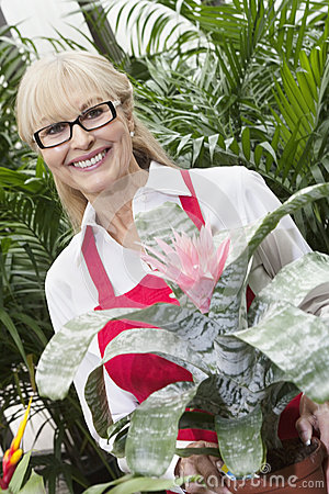 Portrait of a happy senior woman standing behind flower plant in greenhouse