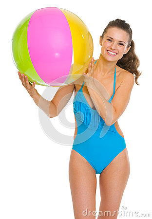 Smiling young woman in swimsuit with beach ball