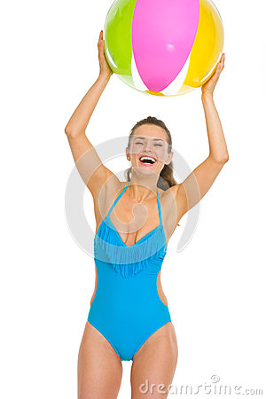 Happy woman in swimsuit playing with beach ball