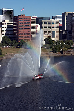 Fireboat in front of marina, city.