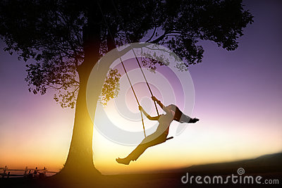 Silhouette of happy young woman on swing