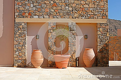 Stone wall with tree terracotta pots (Greece)
