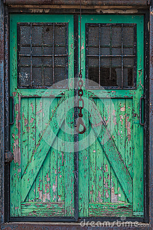 Old wooden warehouse door with a crane hook in front
