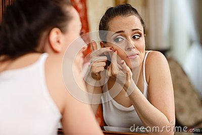 Woman finding an acne on her cheek
