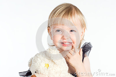 Smiling little girl pointing at her healthy white teeth