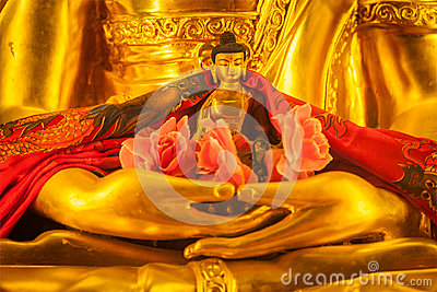 Small Buddha Sakyamuni statue in hands of large