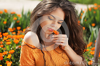 Beautiful brunette woman with colored makeup smelling flower, ov