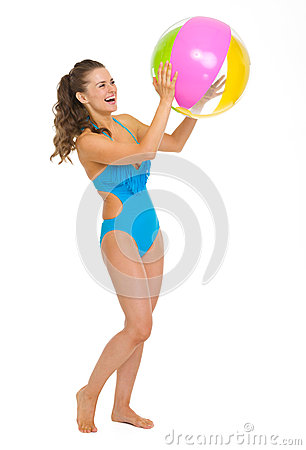 Happy young woman in swimsuit playing with beach ball