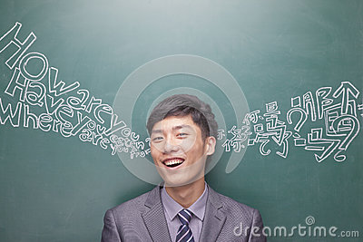 Portrait of smiling young businessman in front of black board with Chinese and English script coming from each ear