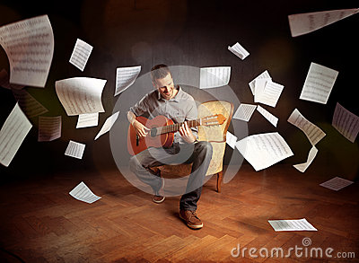 Young man playing guitar with sheet music flying around him