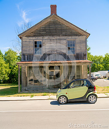 Smart Car in front of old wooden house.