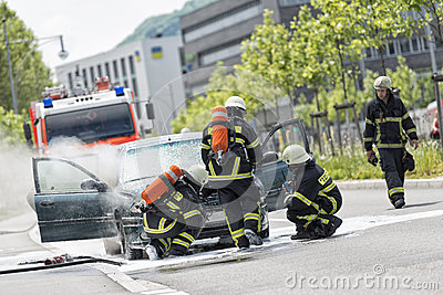 Burning motor vehicle been put out by firemen in protective clot