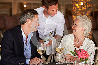 Waiter Serving Wine To Senior Couple In Restaurant