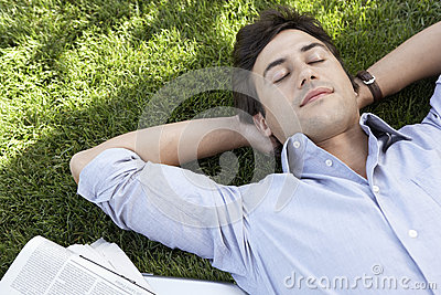 Relaxed Businessman Lying On Grass At Park