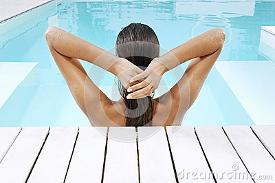 Woman In Swimming Pool At Poolside Pulling Back Hair