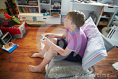 Young Boy Playing Video Game In Bedroom