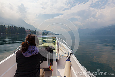 Woman piloting motor boat on a smooth, peaceful, beautiful