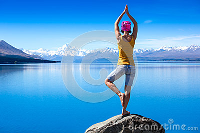 An attractive young woman doing a yoga pose for balance and stretching near the lake
