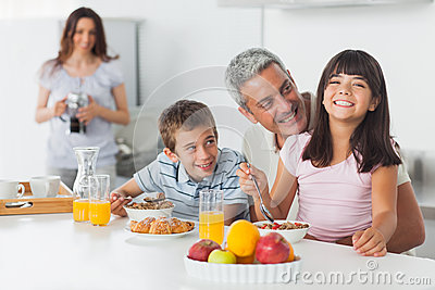 Smiling family eating breakfast in kitchen together