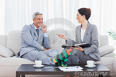Funny businessman wearing stripey socks and laughing with his co