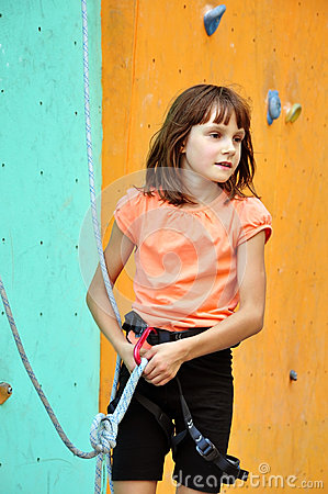 Child with climbing equipment against the training wall