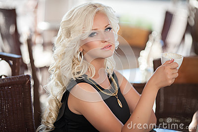 Beautiful woman drinking coffee in cafe restaurant, girl in bar, summer vacation. Pretty blond at breakfast. happy smiling woman