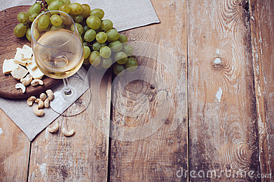 Glass of white wine, grapes, cashew nuts and soft cheese