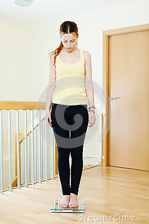 Serious girl standing on bathroom scales