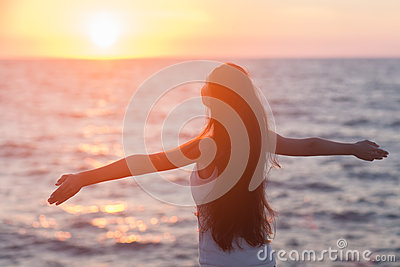 Free woman enjoying freedom feeling happy at beach at sunset.