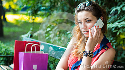 Young  woman sitting on a bench with colorful shopping bags and mobile phone.