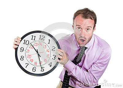 Businessman, executive, leader holding a clock, very determined, pressured by lack of time, running out of time, late for the meet