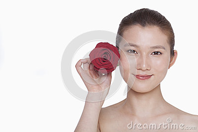 Smiling young woman holding up a red rose next to her ear, studio shot