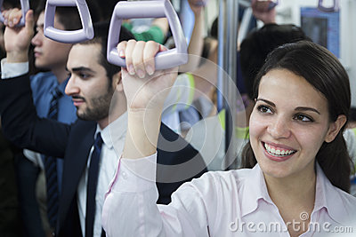 Portrait of smiling young businesswoman standing on the subway, looking away