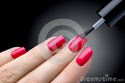 Beautiful manicure process. Nail polish being applied to hand, polish is a pink color.