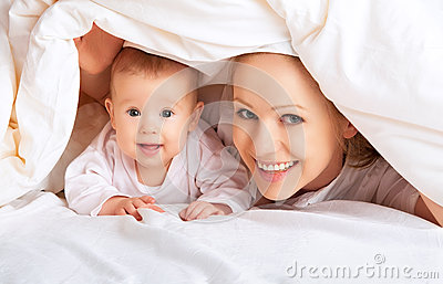 Happy family. Mother and baby playing under  blanket